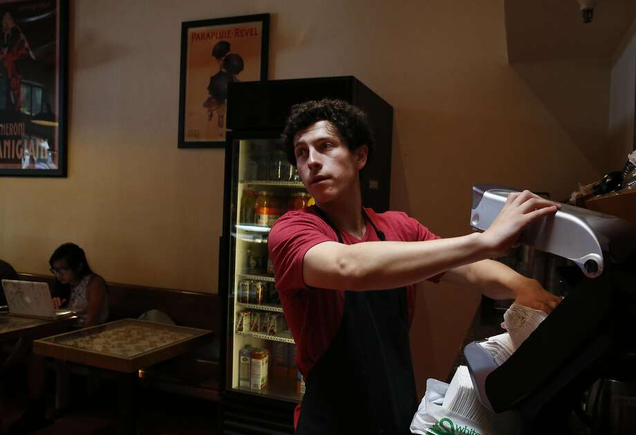 Employee Gabriel Moreno restocks the napkin dispenser at the Beanery in Berkeley. Photo: Leah Millis, The Chronicle
