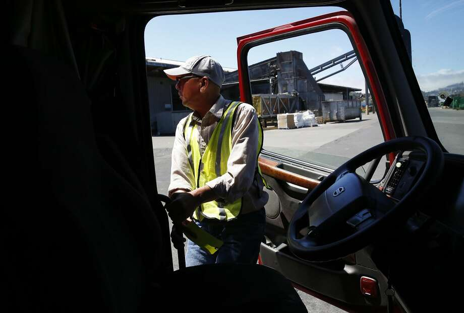 Ted Chen, 56, jumps out of his truck to check the back after docking at Recology in San Francisco. Photo: Leah Millis, The Chronicle