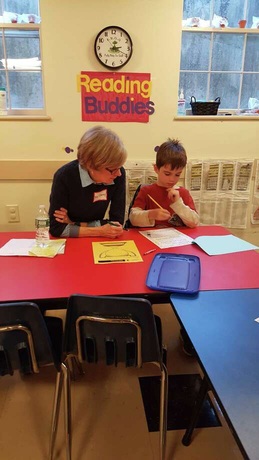 Volunteer Barbara Clancy helps a child with their creative project following a read-aloud session. Photo: Contributed Photo