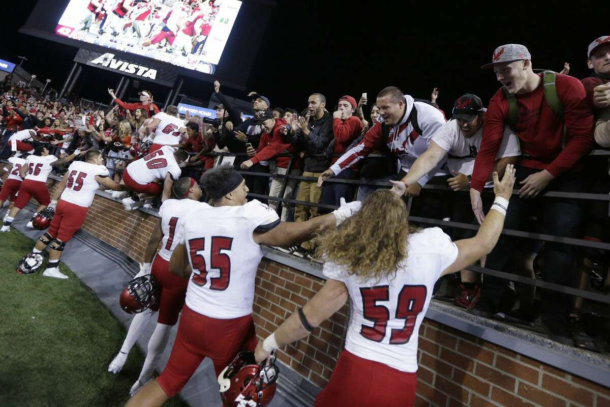 Eastern Washington linebacker Kurt Calhoun (59), defensive lineman Andre Lino (55) and teammates celebrate with fans after winning an NCAA college football game against Washington State in Pullman, Wash., Saturday, Sept. 3, 2016. Eastern Washington won 45-42. (AP Photo/Young Kwak)