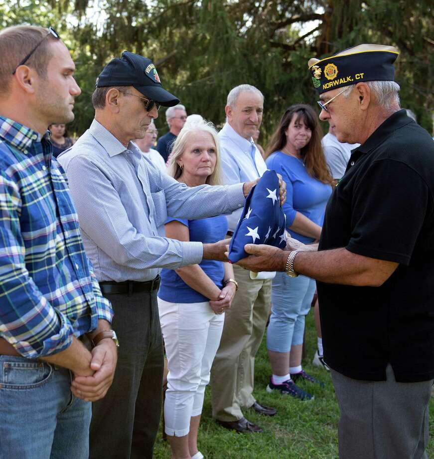 Sergeant at Arms Dan Caporale gets a flag from Vincent Costabile, the youngest son of World War II U.S. Navy veteran Peter Costabile, during the Veteran of the Month Flag Ceremony at American Legion Post 12 in Norwalk, on Sunday. The flag will fly at the Post during the month of September. A decorated Navy Signalman 2nd Class, Costabile served from 1929 to 1931 and again from 1942 to 1945. After two honorable discharges, Costabile served again in the Naval Reserves. Photo: Lindsay Perry / For Hearst Connecticut Media / Norwalk Hour Freelance