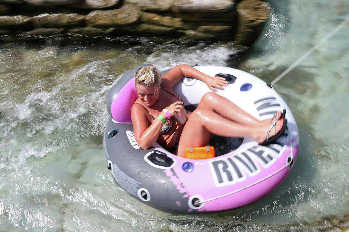 A woman rides a chute on the Comal River by Prince Solms Park in New Braunfels, Texas, Sunday, Sept. 2, 2016. It is the last weekend of summer and people took to the water.