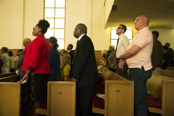 """Members of the congregation stand during Sunday service at Third Baptist Church where San Francisco quarterback Colin Kaepernick was scheduled to speak in San Francisco, Calif. on Sunday, Sept. 4, 2016. Kaepernick was unable to attend due to """"rigors of training,"""" according to Rev. Amos Brown."""