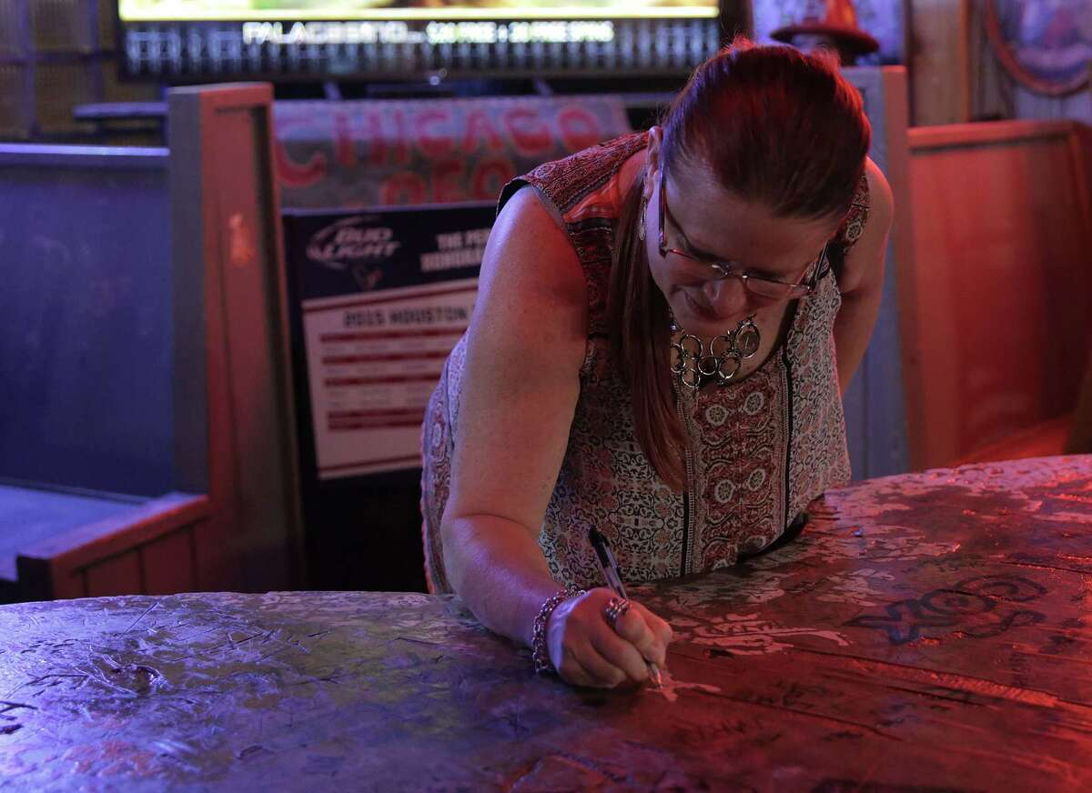 Nora Meadows signs the famous Texas table at Kay's Lounge, her husband proposed to her at the table and the couple are purchasing it .