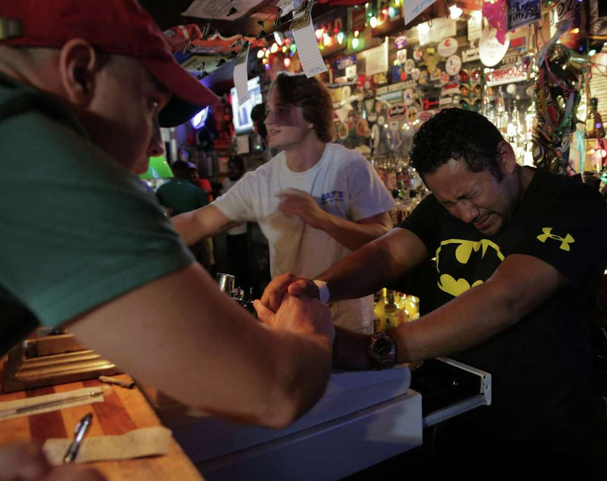 """Bartender Mario Morales gets encouragement from patrons as he starts closing tabs after last call at Kay's Lounge, the oldest bar in Houston on Sunday, Sept. 4, 2016. Morales had been working at the bar for 14 years. """"These people, the regulars, the people who clean, they are all my family,"""" said Morales."""