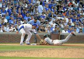 San Francisco Giants' Joe Panik, right, is safe at third base as Chicago Cubs third baseman Kris Bryant (17) makes a late tag during the eleventh inning of a baseball game, Sunday, Sept. 4, 2016, in Chicago. (AP Photo/David Banks)