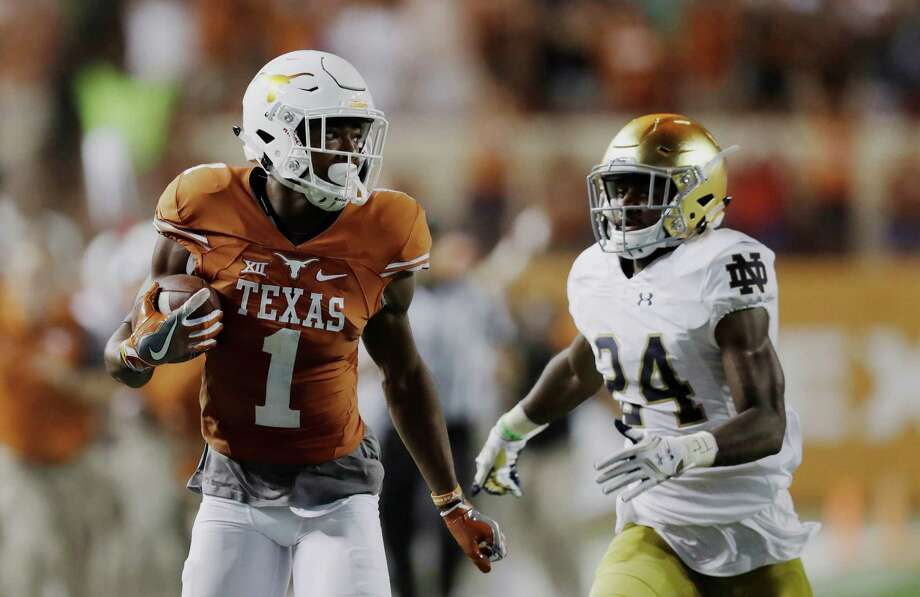 Texas wide receiver John Burt (1) runs from Notre Dame defensive back Nick Coleman during a 72-yard touchdown reception in the second half of an NCAA college football game, Sunday, Sept. 4, 2016, in Austin, Texas. (AP Photo/Eric Gay) Photo: Eric Gay, Associated Press / Copyright 2016 The Associated Press. All rights reserved.