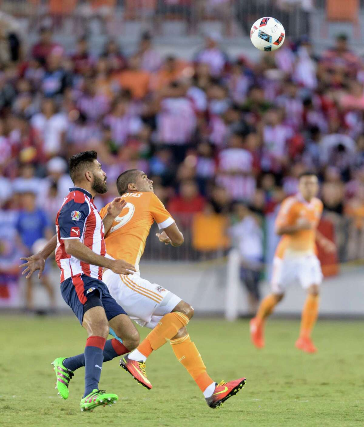 Mauro Manotas (19) of the Houston Dynamo looks for a header in front of Nestor Caldgron (18) of C. D. Guadalajara in a friendly soccer match on Sunday, September 4, 2016 at BBVA Compass Stadium in Houston Texas.