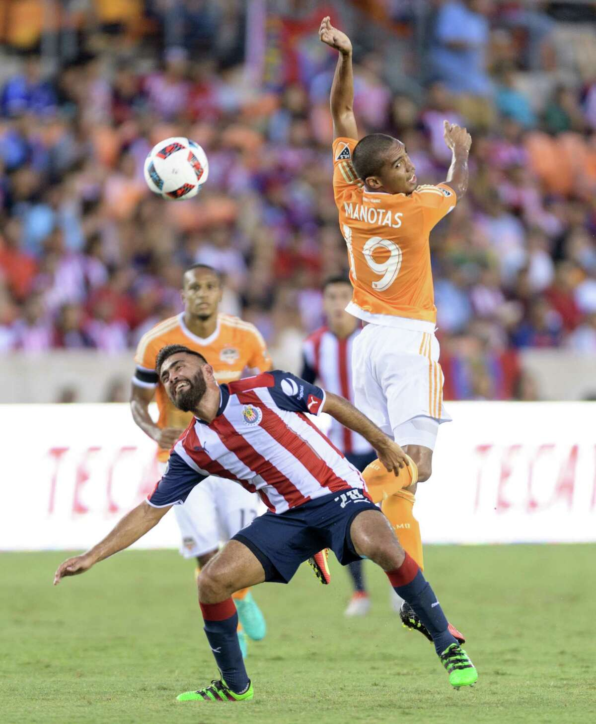 Mauro Manotas (19) of the Houston Dynamo heads the ball towards the goal in front of Miguel Basalt (28) of C. D. Guadalajara in a friendly soccer match on Sunday, September 4, 2016 at BBVA Compass Stadium in Houston Texas.