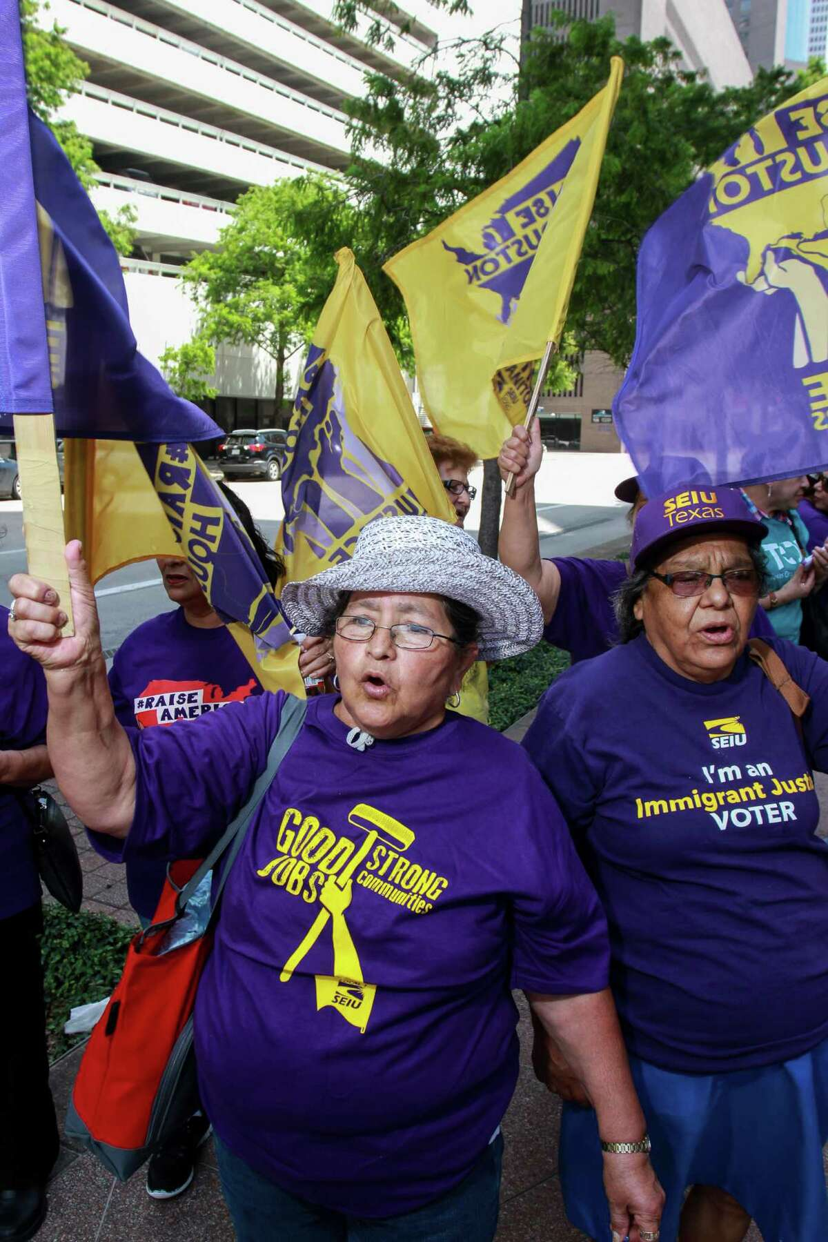 Francisca Reyes, left, and Austroberta Rodriguez march in a rally for janitors in June.