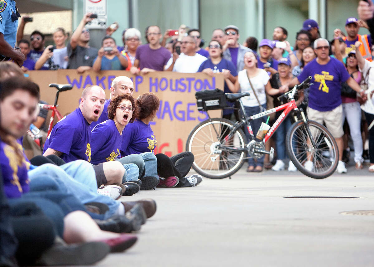 Protesters in 2012 sit in the intersection of Dallas and Smith in support of better pay for janitors.