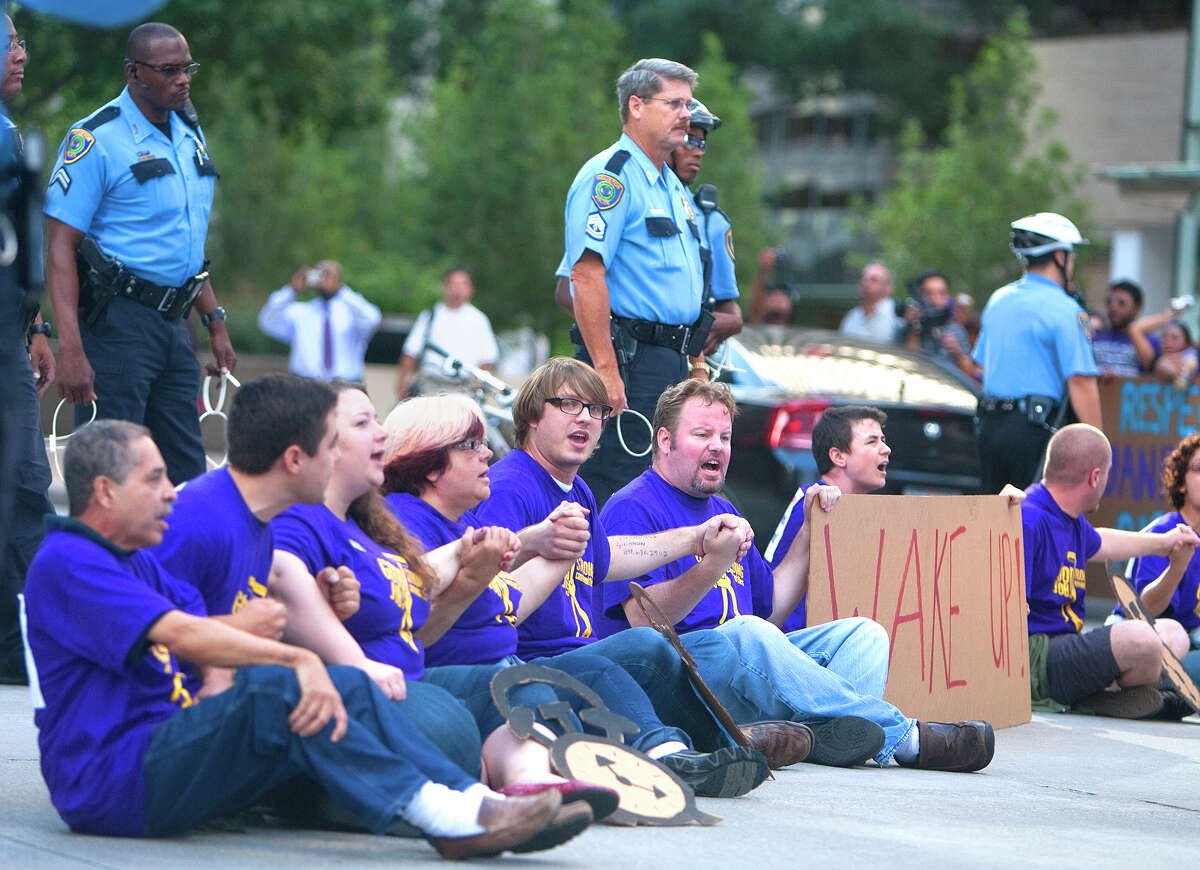 Protestors sit in the intersection of Dallas and Smith Streets in protest of janitors' current wages Wednesday, August 1, 2012, in Houston. Civil rights and labor activists are currently demonstrating civil disobedience and supporting janitors who are entering their fourth week of an unfair labor practices strike. (Cody Duty / Houston Chronicle)