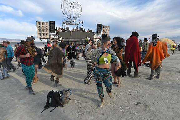 Patiers dance the morning away at Burning Man on the Black Rock Desert near Gerlach, Nev. Monday, Aug. 29, 2016. (Andy Barron/Reno Gazette Journal via AP)