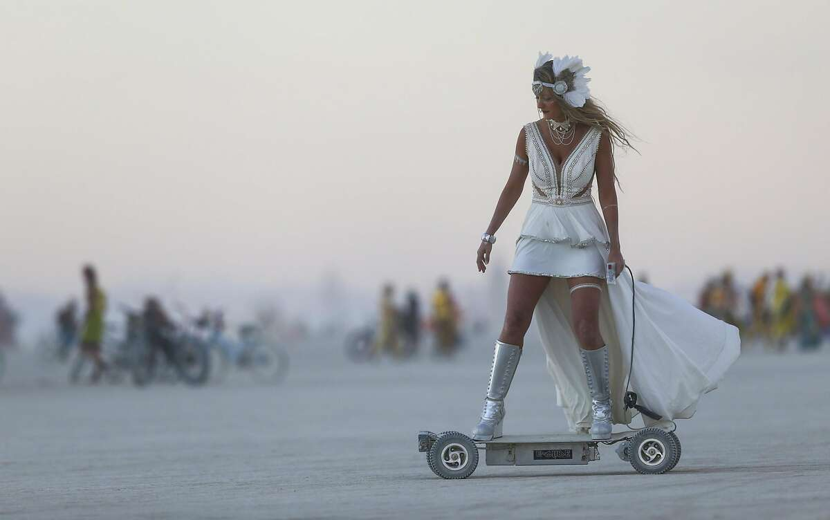 In this Wednesday, Aug. 31, 2016 photo, a woman rides an electric scooter during Burning Man at the Black Rock Desert north of Reno, Nev. (Chase Stevens/Las Vegas Review-Journal via AP)