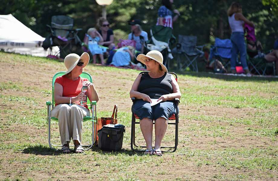 Catherine Ariel of Wilton, left, and her sister Christine Flick of Saratoga Springs find a sunny spot on the lawn to listen to the United States Navy Band Northeast Ceremonial Band perform a concert highlighting musical selections meant to inspire patriotism during a free Labor Day concert at Saratoga Performing Arts Center on Monday, Sept. 5, 2016 in Saratoga Springs, N.Y.  The sisters were there in remembrance of their father Al Flick who was a WWll veteran. (Lori Van Buren / Times Union) Photo: Lori Van Buren / 20037819A