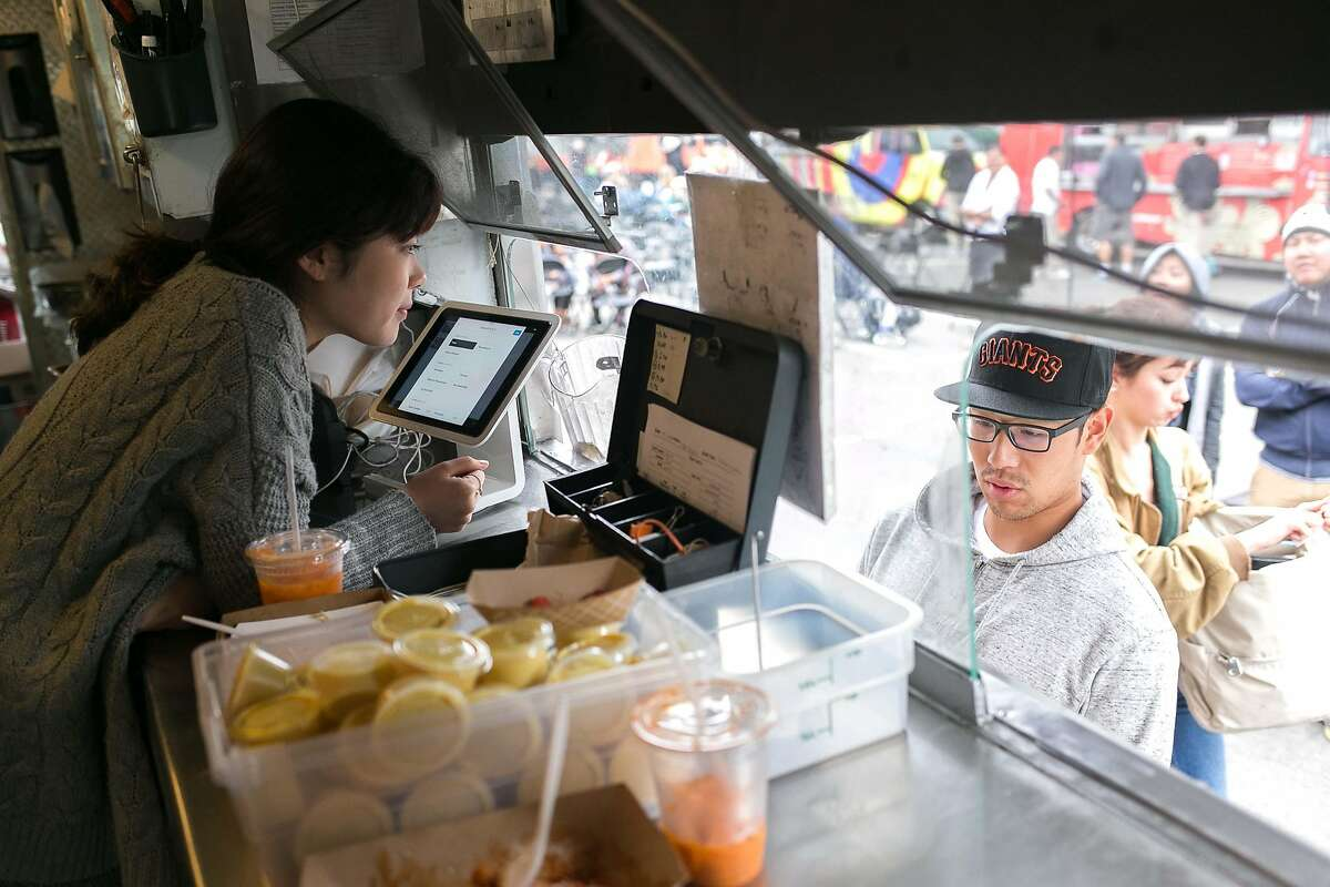 Julie Kim takes an order inside the truck of Kokio Republic in S.F.
