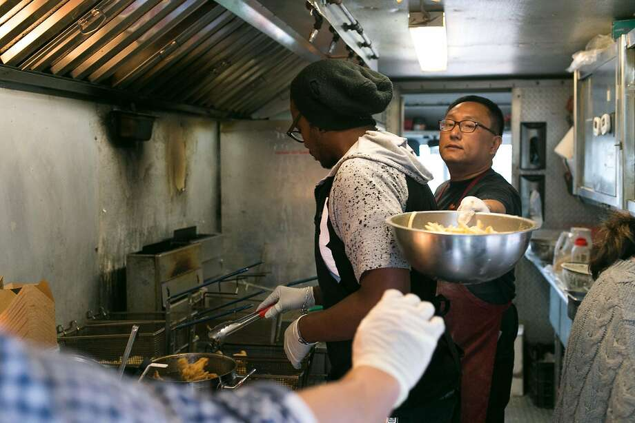 David Han (far right) passes a bowl of fries in the Kokio Republic food truck in S.F. Photo: Jen Fedrizzi, Special To The Chronicle