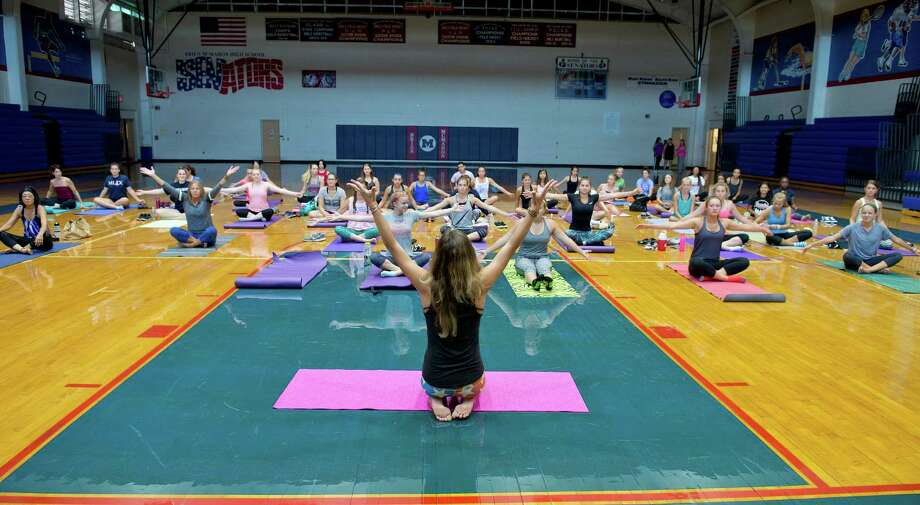 """Lauren Madaffari, a yoga instructor, leads athletes from Brien McMahon High School in a yoga class on Sunday, September 4, 2016. Madaffari is a graduate of Brien McMahon and decided to lead the class at her former school to """"give back to the community that I grew up in and that helped form who I am."""" Photo: Lindsay Perry / For Hearst Connecticut Media / Norwalk Hour Freelance"""