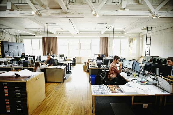 Architects working on design projects at workstations in office