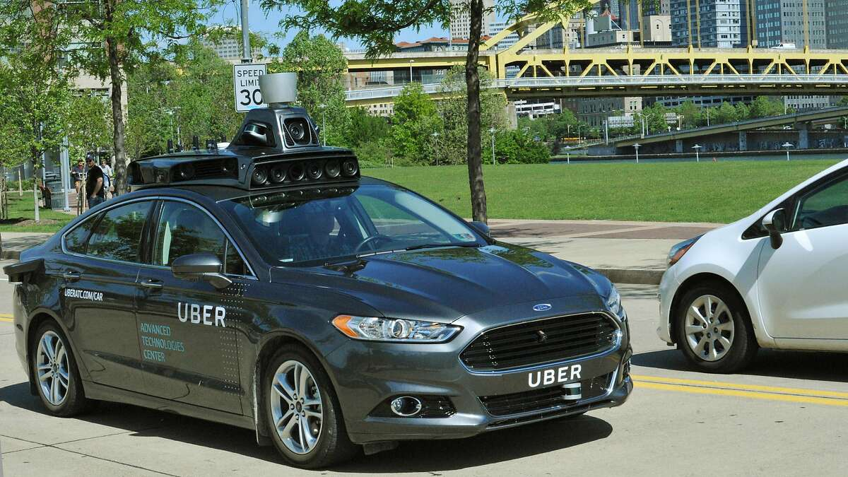 FILE - In this undated file photo provided by Uber, a Ford Fusion hybrid outfitted with radars, laser scanners and high-resolution cameras drives along the streets of Pittsburgh. Uber said Thursday, Aug. 18, 2016, that passengers in Pittsburgh will be able to summon rides in self-driving cars with the touch of a smartphone button in the next several weeks. The high-tech ride-hailing company said that an unspecified number of autonomous Ford Fusions with human backup drivers will pick up passengers just like normal Uber vehicles. Riders will be able to opt in if they want a self-driving car, and rides will be free to those willing to do it, spokesman Matt Kallman said. (Uber via AP, File)