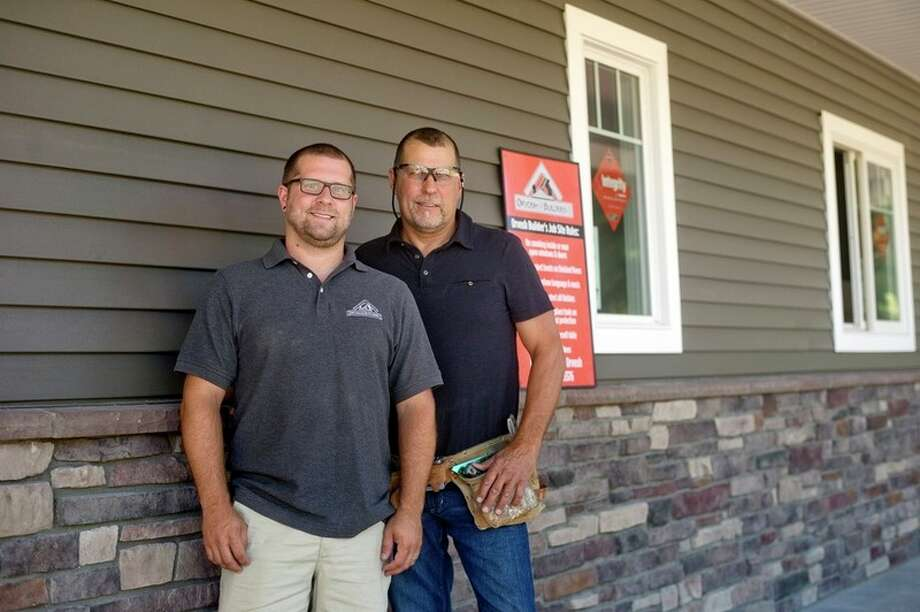Jason Orvosh, left, and his father, Paul, of Orvosh Builders, pose outside a home project they are working on. / Midland Daily News
