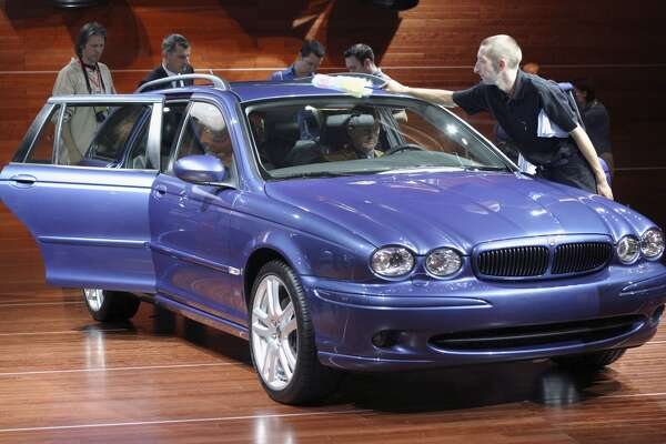 FRANKFURT, GERMANY - SEPTEMBER 9: A maintenance worker sweeps dust off the new Jaguar X-Type Estate car as journalists take a closer look September 9, 2003 at the Frankfurt Auto Show in Frankfurt, Germany. The X-Type Estate is Jaguar's first station wagon. (Photo by Sean Gallup/Getty Images)