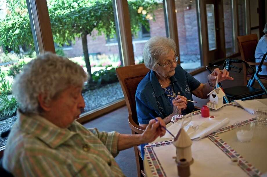 Residents Nancee Most, 85, left, and Marian Reinke, 89, right work on an arts and crafts project at King's Daughters Home.