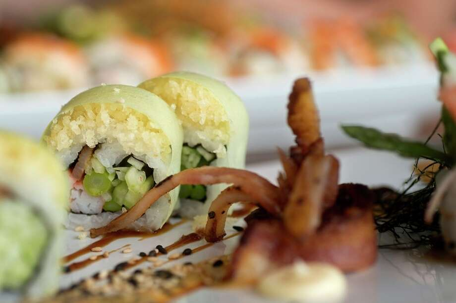 The sexy bacon roll, made of hickory smoked bacon, cucumber, asparagus, crab stick, tempura crunch in soy paper served with fantasy sauce, eel sauce and a creamy garlic sauce and shredded nori, is one of the signature rolls offered at Maru Sushi and Grill.