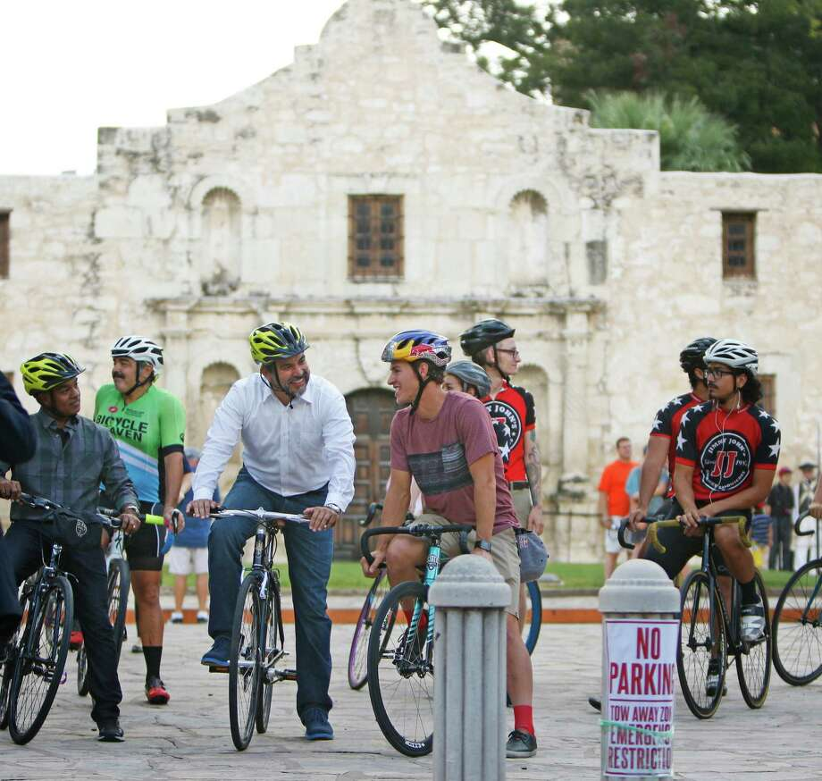 """San Antonio City Councilman Roberto Treviño, (in white shirt), and champion  cyclist Addison Zawada chat Tuesday before leading a """"course tour"""" on bicycles  to show off the nine-turn, half-mile Red Bull Last Stand criterium road race. It  will take place in downtown San Antonio in October. Photo: Ron Cortes, Freelance / For The San Antonio Express-News"""