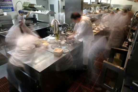 AQUA28B-C-17APR02-LV-CG --- The kitchen of Aqua Restaurant in San Francisco, Ca., on Friday, April 12, 2002 is a blur of activity as the dinner rush begins.  Whether there for romance, business, to impress or just because they love great food in the quiet dining room, patrons at Aqua hardly know the choreographed chaos behind the kitchen doors--a frantic dance that ultimately brings tremendous food to their tables.   (PHOTO BY CARLOS AVILA GONZALEZ/THE SAN FRANCISCO CHRONICLE)