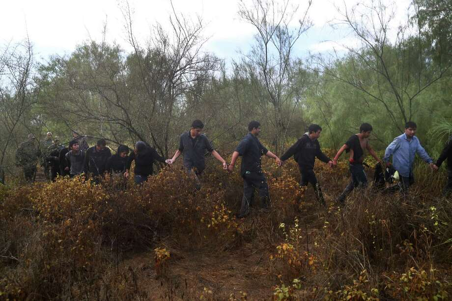 Captured by Border Patrol agents, detained immigrants are led through the brush of Roma. A reader says it is time to enact immigration reform. Photo: John Moore /Getty Images / 2016 Getty Images