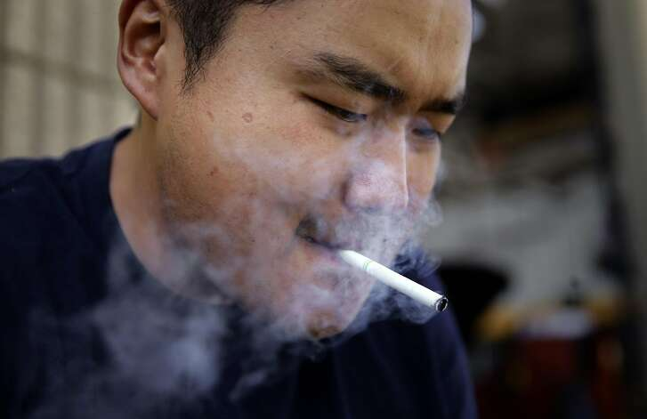 Urgen Sherpa smokes a cigarette along San Pablo Ave. in Richmond, Calif. on Tues. Sept. 6, 2016. California's proposition 56, the cigarette initiative is passed would add $2 to a pack of cigarettes which would go to health-care programs, smoking prevention and research.