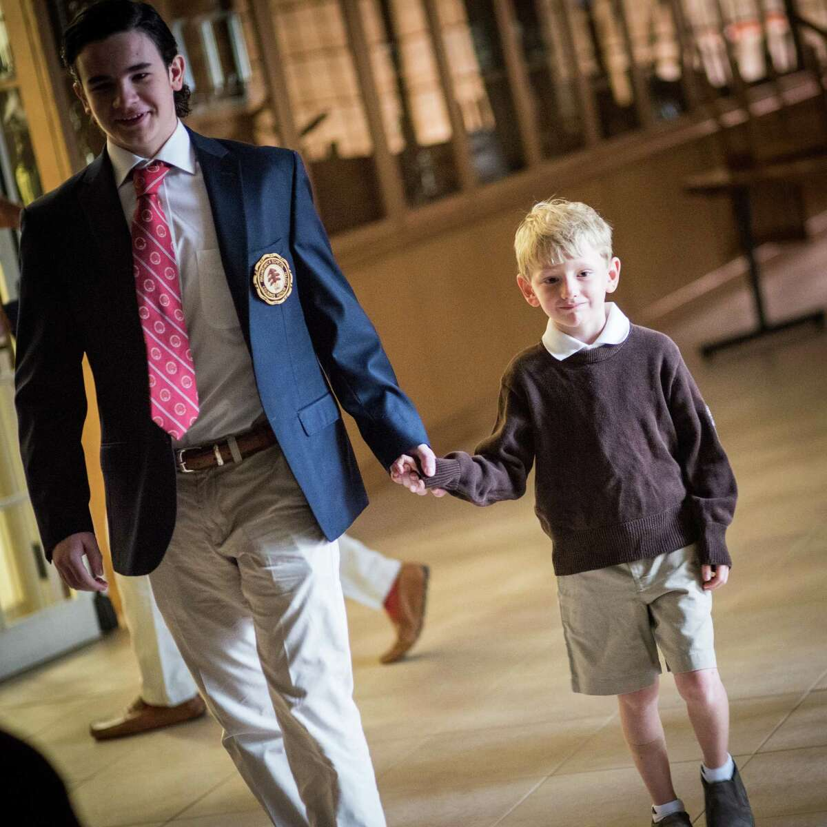 Senior Jack Stefanou and first-grader Gavin Kirsch prepare process into the beginning of opening exercises for Brunswick's 114th school year.