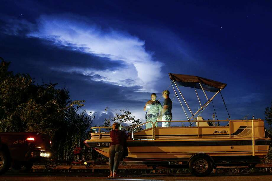 Lightning fills the sky as Texas Game Warden Dustin Dockery, center, talks to a man and woman who were pulling their boat out of the Trinity River at the Wallisville Lake Project Friday, August 26, 2016. The man and woman admitted to fishing without licenses and littering and Dockery also discovered that the boat registration was expired and the truck they were driving did not have insurance. Photo: Michael Ciaglo, Houston Chronicle / © 2016  Houston Chronicle
