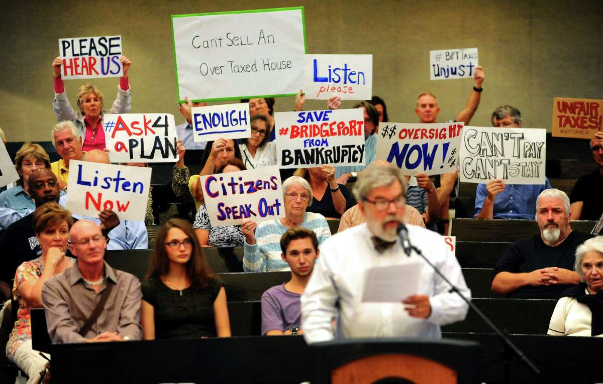 About two dozen members and supporters of Citizens Working for a Better Bridgeport hold up signs to protest increased taxes during the public comment portian of the Bridgeport City Council meeting at City Hall in Bridgeport, Conn., on Tuesday Sept. 6, 2016. Speaking at the podium on behalf of the group is activist John Marshall Lee.