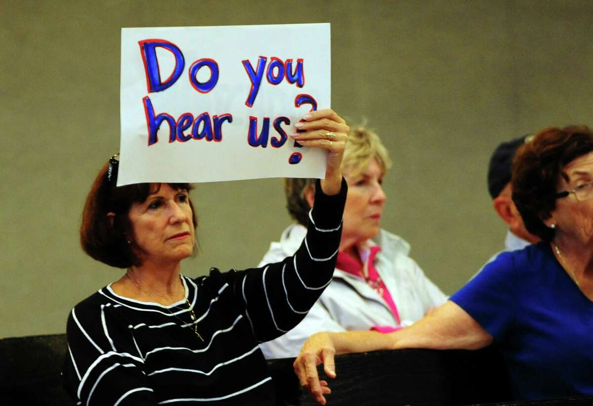 Resident Beverly Balaz holds up a sign to protest increased taxes during the public comment portion of the Bridgeport City Council meeting at City Hall in Bridgeport, Conn., on Tuesday Sept. 6, 2016. The organization Citizens Working for a Better Bridgeport spearheaded a protest against high taxes and other issues during the gathering, with about two dozen members in attendance.