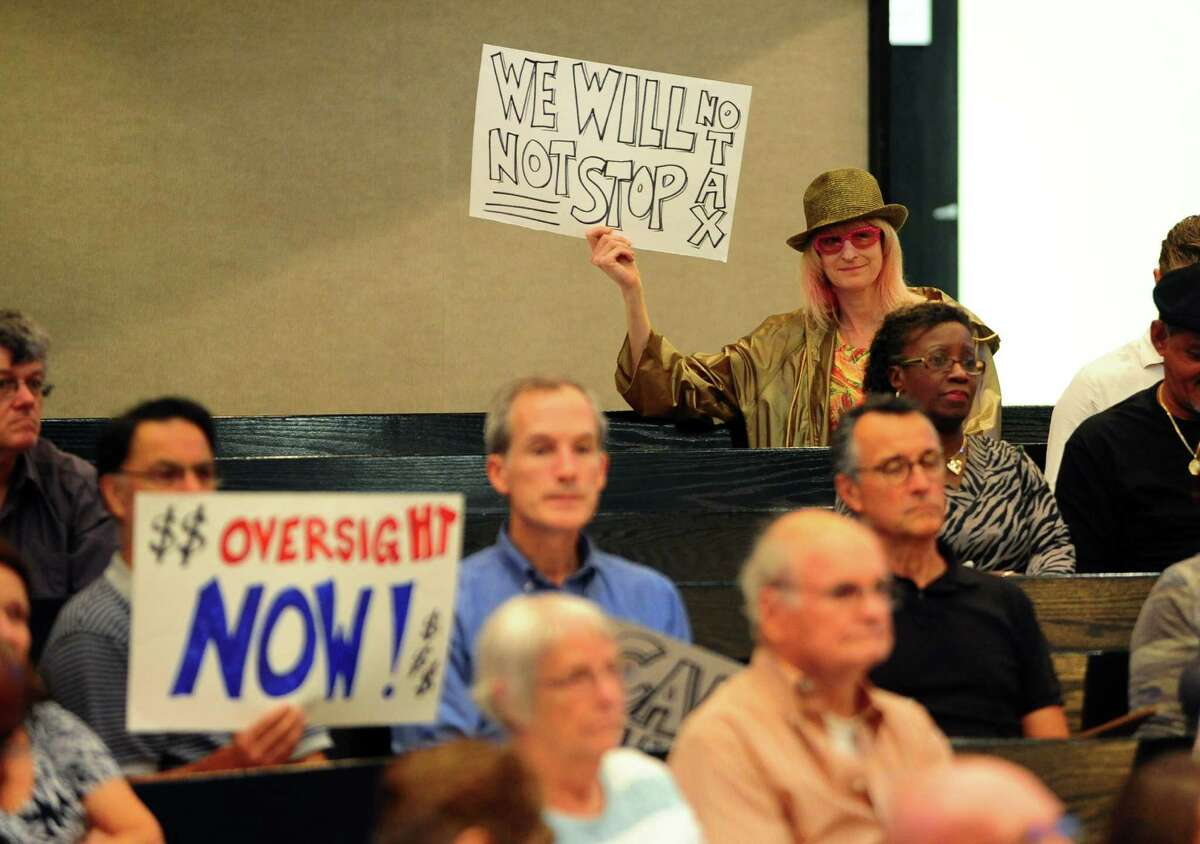 Resident and artist kHyal, in back row, holds up a sign to protest increased taxes during the public comment portion of the Bridgeport City Council meeting at City Hall in Bridgeport, Conn., on Tuesday Sept. 6, 2016. The organization Citizens Working for a Better Bridgeport spearheaded a protest against high taxes and other issues during the gathering, with about two dozen members in attendance.