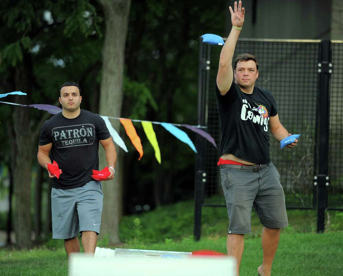 At left, Chris Zingaro of team Children of the Corn watches as Jeff Moreland of team Oh Me So Corny takes his toss during the weekly Tuesday night competition of the Corn Hole League at Mill River Park in Stamford on Sept 6, 2016. About 20 teams compete in the 7 week event sponsored by sponsored by Stamford's Half Full Brewery and Mill River Park Collaborative. in Stamford on Tuesday, Sept 6, 2016.