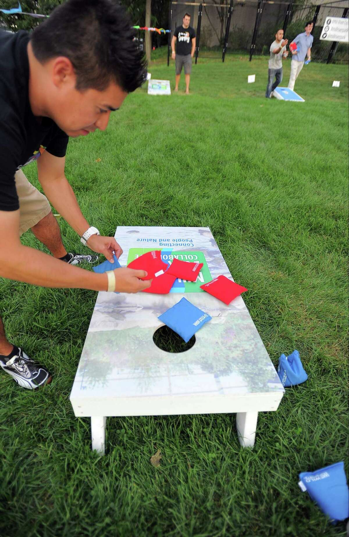 Dan Leyden of team Oh Me So Corny figures out the score during the weekly Tuesday night competition of the Corn Hole League at Mill River Park in Stamford on Sept 6, 2016. About 20 teams compete in the 7 week event sponsored by sponsored by Stamford's Half Full Brewery and Mill River Park Collaborative. in Stamford on Tuesday, Sept 6, 2016.
