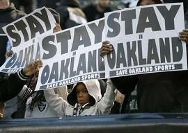 FILE - In this Dec. 24, 2015 file photo, fans hold up a sign for the Oakland Raiders to stay in Oakland before an NFL football game between the Oakland Raiders and the San Diego Chargers in Oakland, Calif. oakland Raiders owner Mark Davis says he wants to move the team to Las Vegas and is willing to spend a half billion dollars as part of a deal for a new stadium in the city. Davis upped the ante in a bid to move the team to this gambling city, appearing Thursday, April 28, 2016, alongside soccer great David Beckham and billionaire casino owner Sheldon Adelson before a committee studying the idea of a $1.4 billion stadium. (AP Photo/Marcio Jose Sanchez)