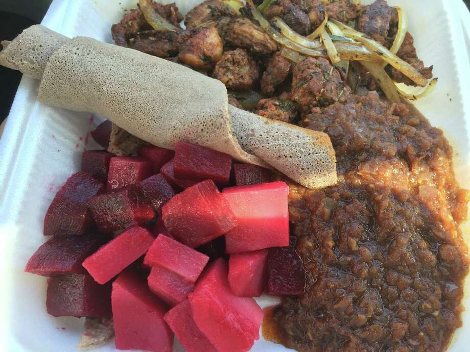 A combo plate at Berbere Ethiopian Cuisine featuring lamb, red lentils and beet and potato salad and an accompanying piece of inerja, the soft Ethiopian flatbread. Photo: Edmund Tijerina /San Antonio Express-News
