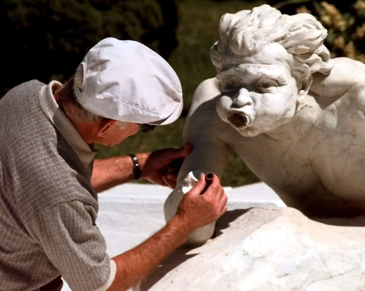 Times Union staff photo by Cindy Schultz -- Wilfred Ganem of Ganem Contracting Corp. examines an exposed water valve on Spit's broken arm on Tuesday, Aug. 31, 1999, at Congress Park in Saratoga Springs, NY. When intact, Spit holds a horn that shoots water at his partner Spat.The marble fountain statues were vandalized Sunday afternoon, Aug. 29. Ganem Contracting, which specializes in masonry restoration, has done previous restoration work in the park.