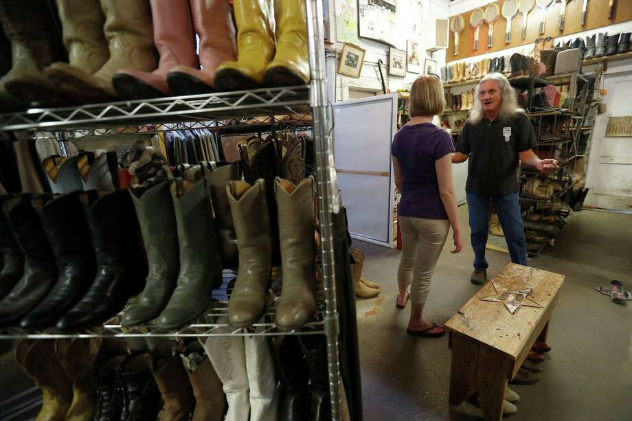 At Texas Junk Co., owner Bob Novotney chats with customer Melissa Leigh.  Novotney is slowly moving inventory to his new location in Moulton, between Houston and San Antonio. Photo: Karen Warren, Houston Chronicle / 2016 Houston Chronicle