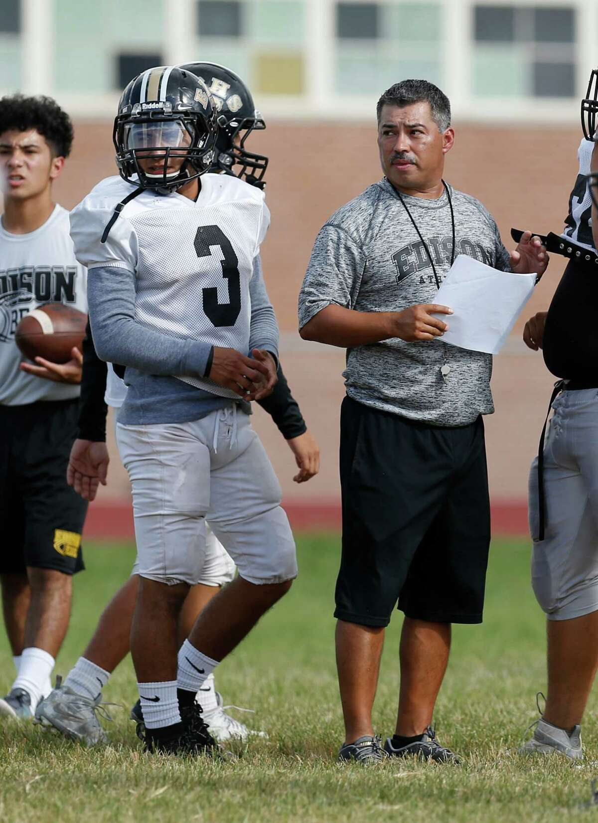 Edison running back Matthew Garcia (3), flanked by coach Albert Torres, practices at the school on Sept. 6, 2016.