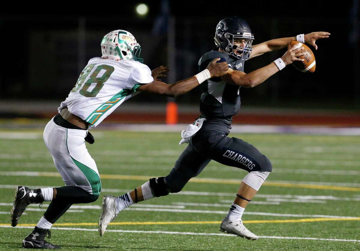 Boerne Champion quarterback Josh Green (right) evades a tackle from Sam Houston's Garland Coleman during a Class 5A Division II playoff game in Boerne on Nov. 13, 2015.