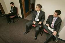 Dressed for success, University of Kansas students Brandon Trice (from left), Tom O'Dea and Ari Shapiro waited for job interviews last month at the University Career Center in Lawrence, Kansas. Experts say many companies are offering incentives to new grads. (Keith Myers/Kansas City Star/KRT)