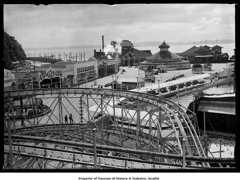 """""""West Seattle's Luna Park was named for Luna, the Roman goddess of the moon. The amusement park was a popular place for Seattleites to swim, dance, and have fun. They could ride on a giant water slide, a rollercoaster, or a carousel, or have a drink at what was advertised as """"the longest bar on the bay."""" They could even see an exhibit of babies in an electric incubator. This photo was taken at Luna Park sometime between 1906 and 1913. The roller coaster loops across the foreground. The bath house is just to the right of the smokestack, behind the steam. The carousel is inside the round building with the turret, near the bath house."""" -MOHAI. Photo courtesy MOHAI, PEMCO Webster and Stevens Collection, image number 1983.10.8281.2. Photo: Courtesy MOHAI"""