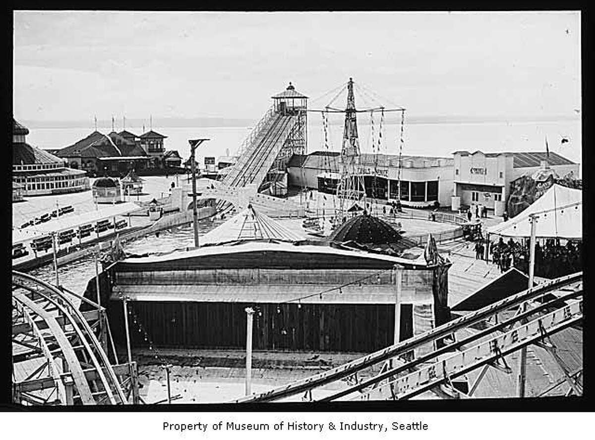 """""""West Seattle's Luna Park was named for Luna, the Roman goddess of the moon. The amusement park was a popular place for Seattleites to swim, dance, and have fun. They could ride on a giant water slide, a roller coaster, or a carousel, or have a drink at what was advertised as 'the longest bar on the bay.' They could even see an exhibit of babies in an electric incubator."""" -MOHAI. Photo, dated circa 1909, courtesy MOHAI, Lantern Slide Collection, image number 2002.3.1482."""