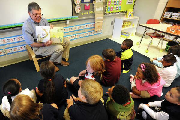 "Joe Nechasek of Shelton reads ""Miss Mingo Weathers the Storm"", by author and illustrator Jamie Harper, to students at Six to Six Magnet School, in Bridgeport, Conn. Sept. 7, 2016. The Bridgeport Public Education Fund organized this reading enrichment program where over 100 volunteers read and distributed the book to first grade students throughout public elementary schools in Bridgeport."