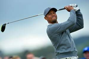 """(FILES) This file photo taken on July 16, 2015 shows US golfer Tiger Woods watches his shot from the 4th tee during his first round on the opening day of the 2015 British Open Golf Championship on The Old Course at St Andrews in Scotland. Tiger Woods said September 7, 2016 he hopes to return to competitive golf next month at a tournament in California, but the 14-time major champion warned his much-anticipated return would depend on his continued recovery. """"My rehabilitation is to the point where I'm comfortable making plans, but I still have work to do,"""" the 40-year-old Woods, who has not played competitively since August 2015, said in a statement.  / AFP PHOTO / Glyn KIRKGLYN KIRK/AFP/Getty Images"""